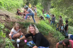 Laura Buzianis helps daughter Dakota dig a hole for a native Keahi tree following a workshop and field demonstration teaching proper planting.